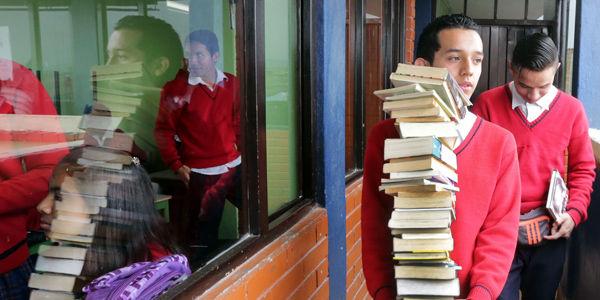 Suena el timbre y los jóvenes van por los libros para la clase.