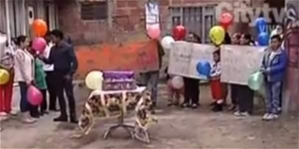 Con bombas y torta, vecinos celebran el cumpleaños 28 de un hueco en la vía
