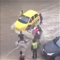Video: policías evitan que taxi sea arrastrado por arroyo