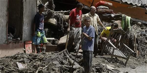 Habitantes limpian los escombros.