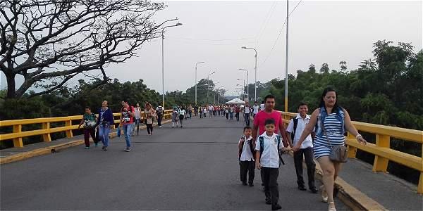 Padres de familia acompañan a sus hijos para cruzar los puentes internacionales.