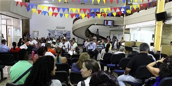 Personas en una oficina de la Dian, a la espera de resolver asuntos relacionados con sus impuestos. Algunos parlamentarios insistirán en el impuesto a los dividendos a través de una proposición.