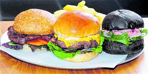 Sándwich de bondiola, hamburguesa y sándwich de tartar de trucha con pan de tinta de calamar.