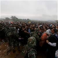 Refugiados sirios intentan cruzar frontera de Grecia a Macedonia en medio de la lluvia