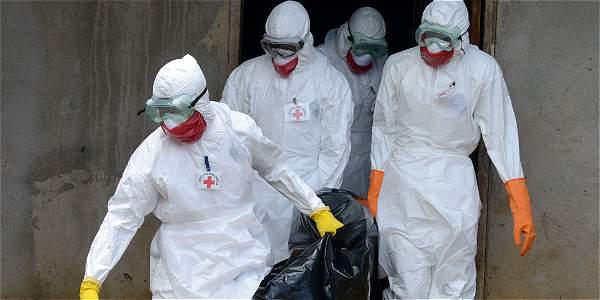 Personal de la Cruz Roja carga el cuerpo de una víctma del ébola en la ciudad liberiana de Banjol.