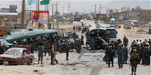 Las autoridades afganas revisan los buses de la Policía en el lugar del atentado en Kabul, Afganistán.