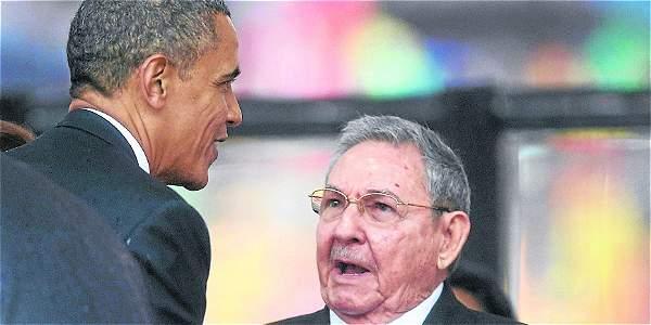 El presidente estadounidense, Barack Obama (i), saludando a su homólogo cubano, Raúl Castro, durante el servicio religioso por la muerte del expresidente sudafricano Nelson Mandela.