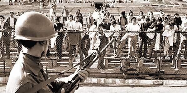 Imagen de 1973, cuando se instauró la dictadura de Augusto Pinochet, en la que se ve a un militar amenazando con su arma a los presos políticos detenidos en el Estadio Nacional.