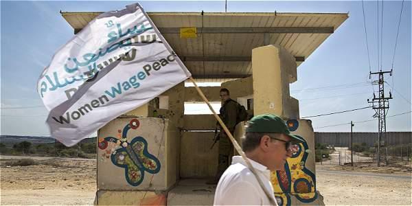 Hombre pasa por delante de una garita de seguridad junto a una sección del muro de separación israelí durante una protesta para pedir la paz entre Israel y Palestina.