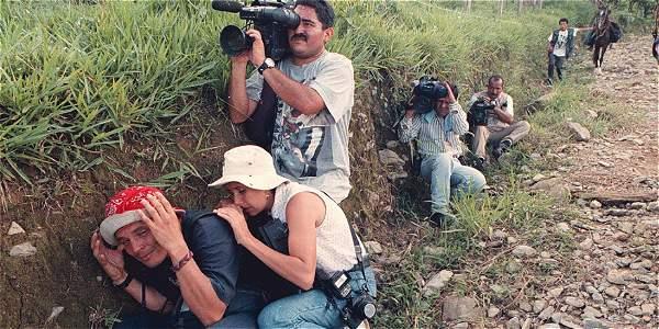 Un grupo de periodista se guarece de las balas, al quedar atrapados  en mitad de una escaramuza, en la vía a la inspección de Los Alpes, zona rural de Villavicencio.