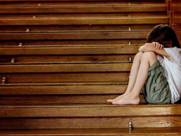 BBC Mundo: Niño con la cara tapada sentado en una escalera