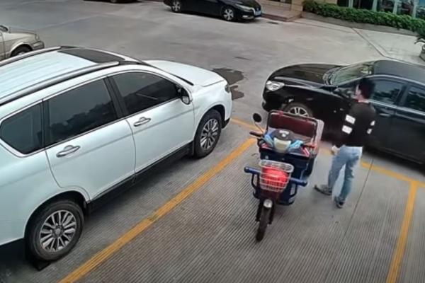 Hombre levanta un carro con las manos para sacar su moto
